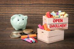 Free Open Enrollment Concept. Colored Papr Scrolls In Wooden Boxes On Dark Wooden Background Stock Photo - 187190640
