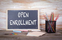 Open Enrollment text on a blackboard. Old wooden table with text Stock Photography