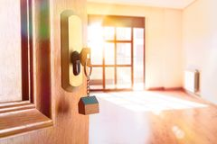 Open entrance door with empty room in the background. Open entrance door detail of a house with keys in the lock and empty room in the background with golden Royalty Free Stock Image
