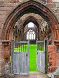 Open Entrance Gate to the Ruins of Sweetheart Abbey, New Abbey, Scotland. The open entrance gate at the ruins of Sweetheart Abbey open the view into the grassy royalty free stock photo