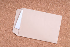 Open Envelope with blank label and paper on cork b Stock Image