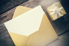 Open envelope with blank paper sheet and gift box. Open yellow paper envelope with blank paper sheet and gift box with ribbon on wooden board Stock Photos