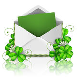 Open envelope with green paper and leaf clover for St. Patrick`s Day. Open envelope with empty green paper, leaf clover and flower for St. Patrick`s Day and Stock Image