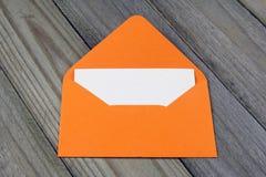 Open envolvió con la tarjeta en blanco en fondo de madera Fotos de archivo libres de regalías