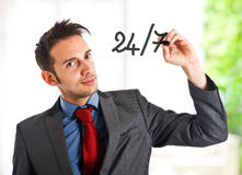 Open every day. Friendly businessman writing 24/7 on the screen Royalty Free Stock Photo