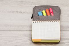 Open exercise book on bag-pencil case with color felt pens and marker on grey wooden boards. Top view with copy space. School supplies. Open exercise book on bag royalty free stock photography