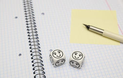 Open exercise book with mood dice (happy) and yellow sticky card Stock Image