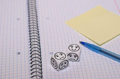 Open exercise book with mood dice and yellow sticky card Royalty Free Stock Image