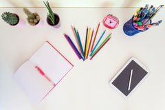 Open exercise book, pencil crayons and tablet on white desk Stock Images