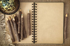 Open exercise book with pencils. On brown background Royalty Free Stock Photography
