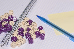 Open exercise book with sticky card, pen and dices Stock Images