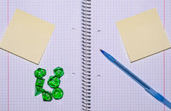 Open exercise book with sticky card, pen and role playing dices Royalty Free Stock Image