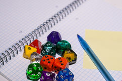 Open exercise book with sticky card, pen and role playing dices Royalty Free Stock Photos