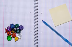 Open exercise book with sticky card, pen and role playing dices Royalty Free Stock Photo