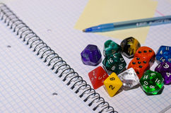 Open exercise book with sticky card, pen and role playing dices Royalty Free Stock Images