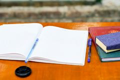 A open exercise book on a table.black stock image