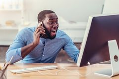 Open eyed African American man talking on phone. Say what. Waist up shot of a surprised millennial man looking at a screen of a PC with his jaw dropped while Royalty Free Stock Image
