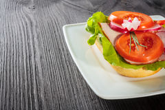 Open faced sandwich with ham. Meat on wooden background Stock Image