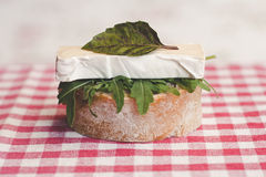 Open-faced sandwich. Slice of a baguette with camembert and rocket Stock Photo