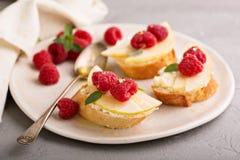 Open a fait face à des sandwichs avec du fromage, les poires et la framboise Photographie stock libre de droits