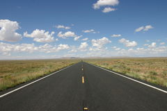 Open feeling and blue skies. Driving down a open road on a summer day with no one around Stock Photography
