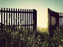 Open fence. An old wooden fence with an open gate door Royalty Free Stock Photography