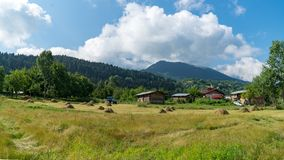 An open field of farm with piles of straw and a tractor in Artvin, Turkey stock photos
