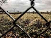 Open field on the other side of the fence. In a cloudy day stock photography