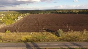 Open field and road. The quadcopter flies by along the field. Behind the field trees are visible. Vol of the field lasts the power line. Before the field the stock footage