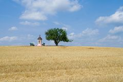 Open fields landscape with little christian chapel on a hill by the tree. Royalty Free Stock Photos