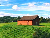 Open filed in the summer with a red barn. In West Cornall New England Connecticut United States stock photo