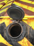 Open filler cap on an old tank. Filler opening on an old and rusted yellow and black tank, with an open cap royalty free stock image