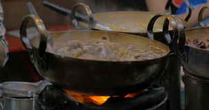On open fire in cauldrons cooking east asian cuisine stock footage