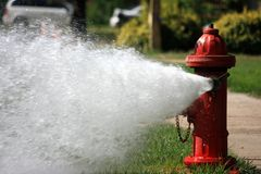 Open Fire Hydrant Gushing High Pressure Water. A close-up photo of a red fire hydrant left open to gush a high pressure stream of water into a residential Royalty Free Stock Image