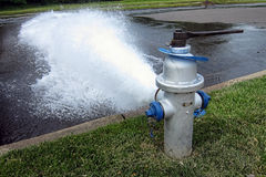 Open Fire Hydrant Plug Gushing High Pressure Water. Firefighting safety fire hydrant plug open with a wrench and gushing huge spray flow of water in a city royalty free stock photos