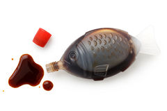 Open fish shaped take away soya sauce isolated on white from abo. Ve. Spilled sauce Royalty Free Stock Images