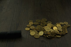 Open flashlight to find hair on pile of gold coins Stock Image