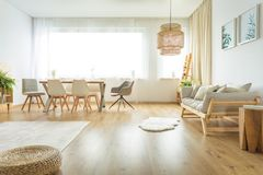 Multifunctional dining and living room. Open flat design with natural, wooden furniture in multifunctional dining and living room stock photos