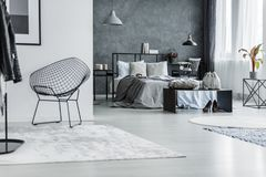 Open flat with metal chair. Open flat interior with black, metal chair in the hall and gray bed in the bedroom Stock Images