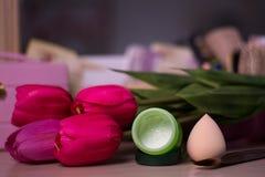 Open fles gezichtsroom met spons op de achtergrond van het tulpenonduidelijke beeld stock foto's