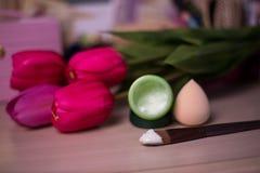 Open fles gezichtsroom met spons op de achtergrond van het tulpenonduidelijke beeld Royalty-vrije Stock Fotografie