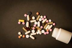 Open fles met verschillende pillen op donkere achtergrond De mening Fr stock afbeelding