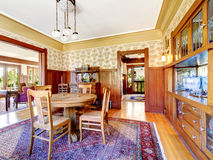 Open floor plan antique dining area with wooden panel trim Stock Photo