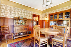 Open floor plan antique dining area with wooden pannel trim Stock Image