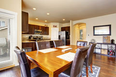 Open floor plan dining area connected to modern kitchen Royalty Free Stock Images