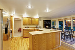 Open floor plan kitchen interior with brown cabinets and hardwood floor Royalty Free Stock Images