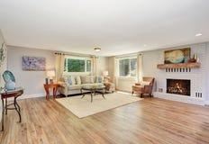 Open floor plan living room interior in white tones with hardwood floor. Stock Photos