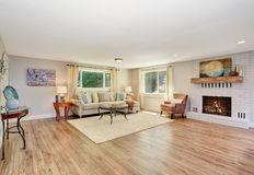 Open floor plan living room interior in white tones with hardwood floor. Also white brick fireplace. Northwest, USA Stock Photos
