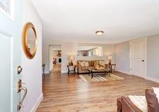 Open floor plan living room interior in white tones with hardwood floor. stock photo