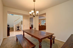 Open floor plan. View of dining room with Carved wooden table and living room Stock Photography